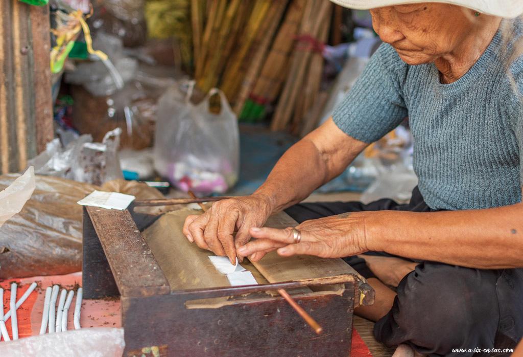 Une vieille femme roule des cigarettes et l'apprend aux enfants à Battambang-Cambodge