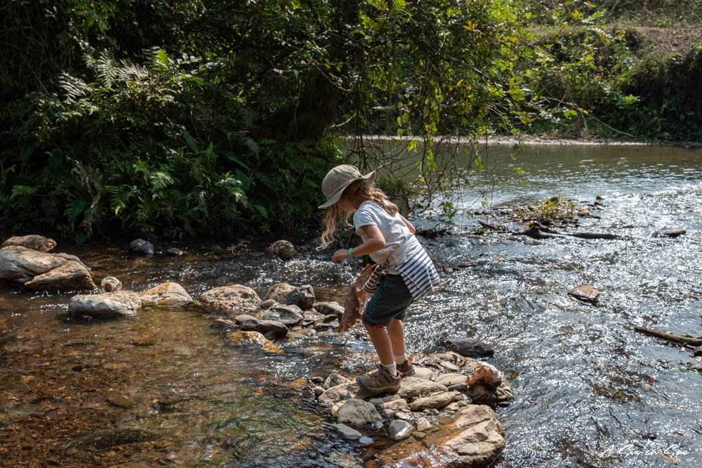 Alice traversant une rivière pour accéder au village de Houey Sen au Nord du Laos